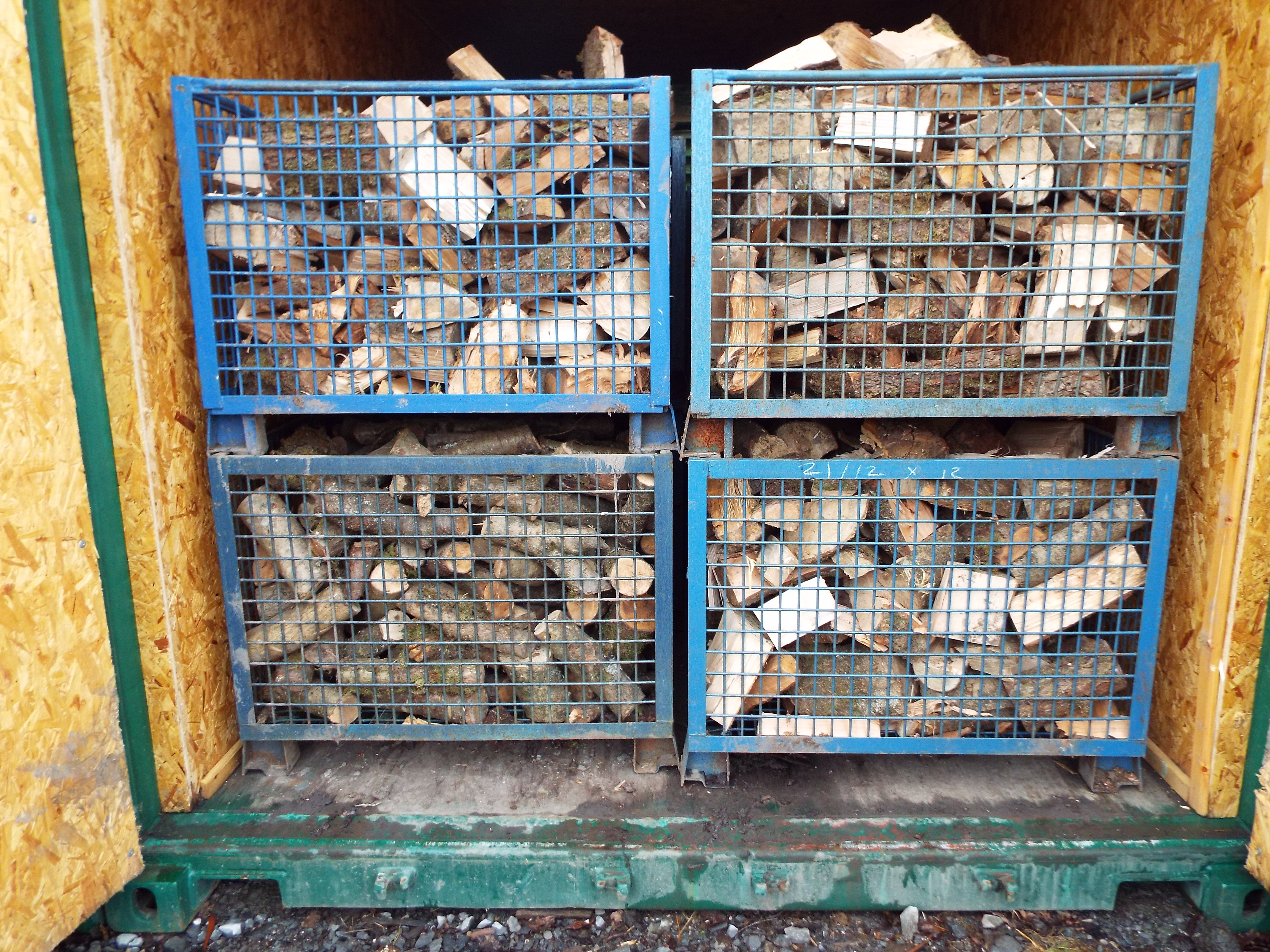 Dried logs stored in lined industrial container.